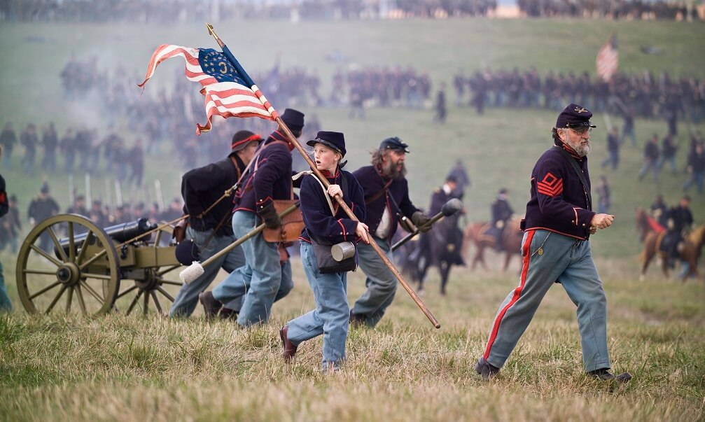 Civil War reenactors playing Union artillery soldiers run across the Cedar Creek Battlefield in the Shenandoah Valley of Virginia, pursued by Confederate soldiers who have overwhelmed their position. The actual Battle of Cedar Creek took place on October 19, 1964