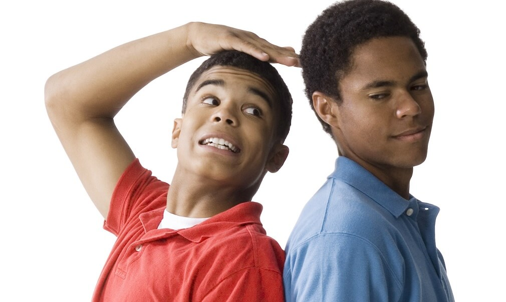 Profile of a teenage boy and a young man standing back to back