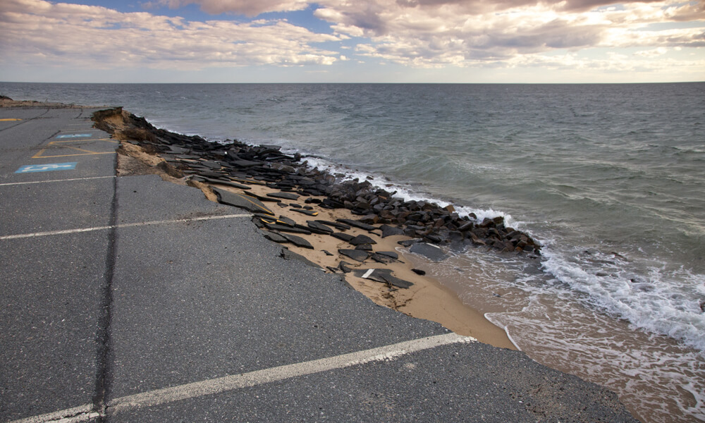 A parking lot next to the ocean being destroyed by erosion due to rising sea levels