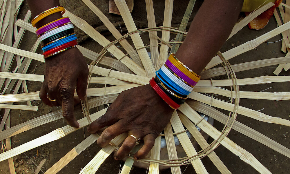 Close view of hands of woman weaving basket
