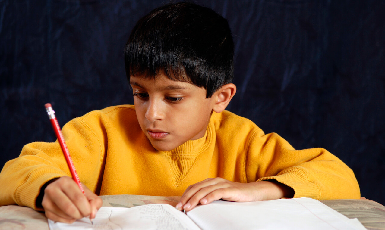 Boy doing homework and writing in a notebook with a pencil