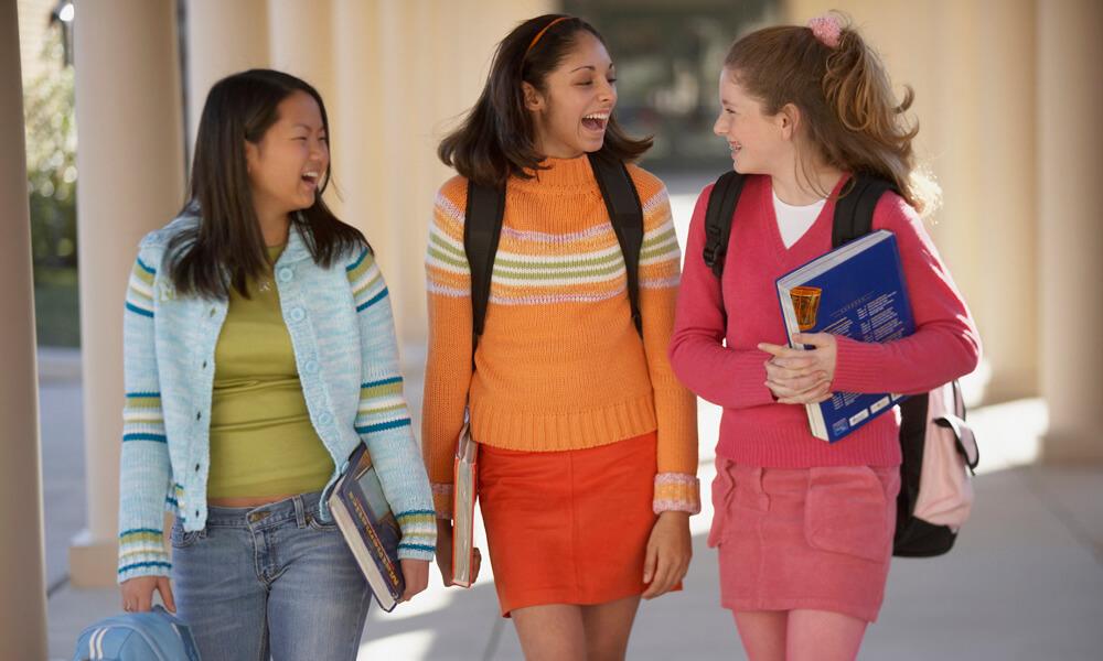 Three teenage girls holding books walking in a hallway