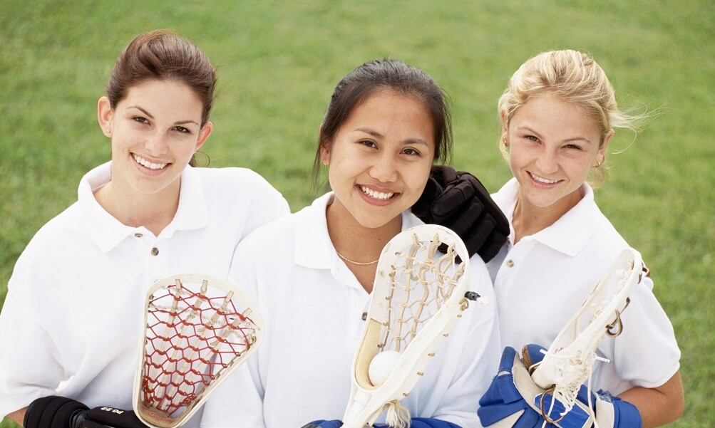 Teenage girls posing with lacrosse equipment