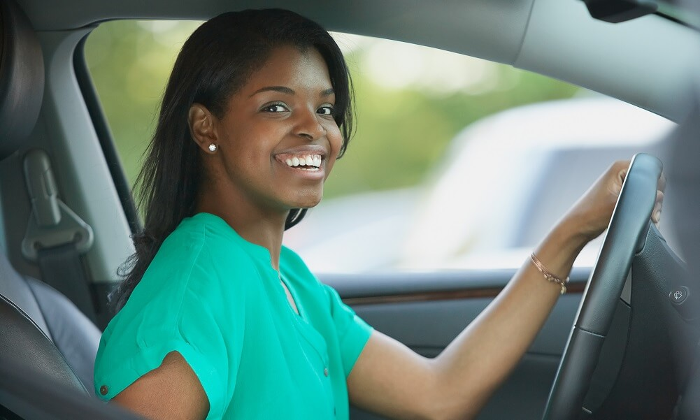 Smiling woman in driver's seat in car