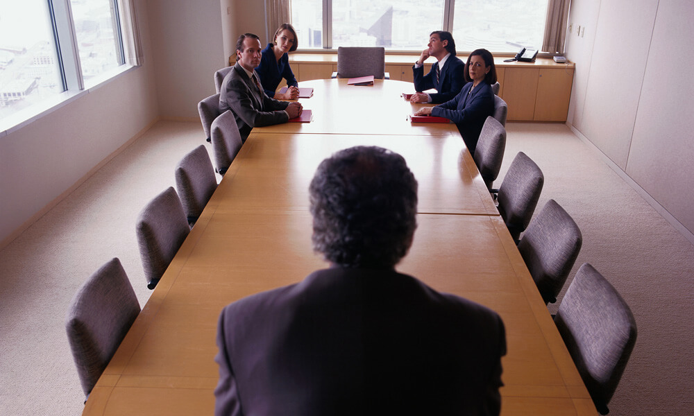 Business executive leaning over a conference table facing employees grouped at the other end of the table