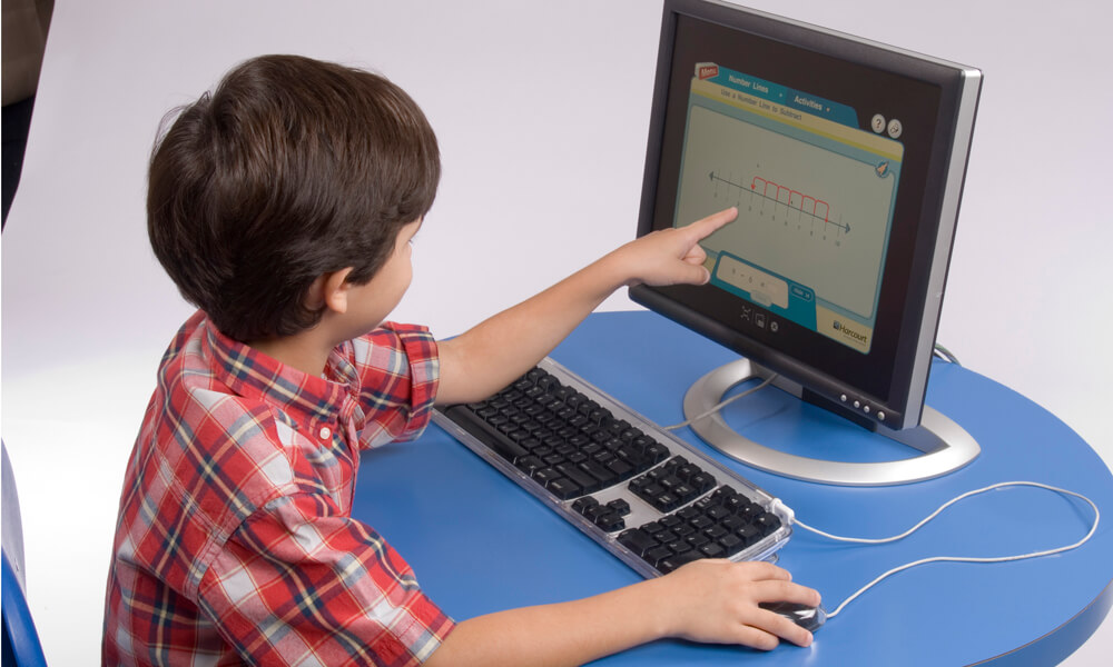 Student working on computer pointing at screen