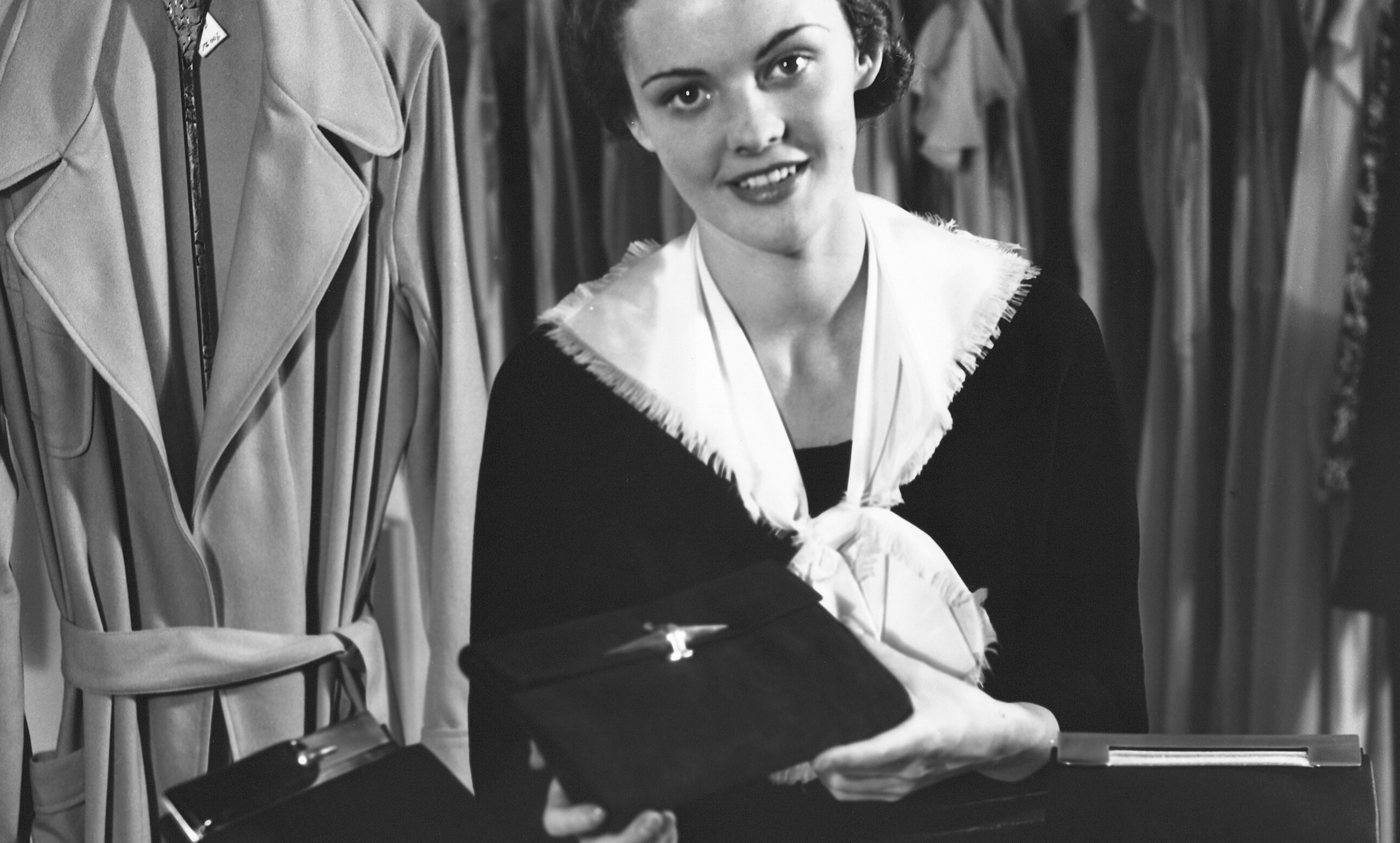 Black and white image of woman selling purses at a store.