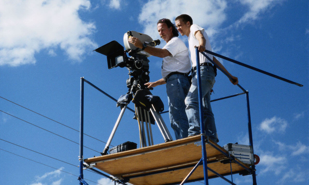 Cameraman and assistant on scaffolding with movie camera