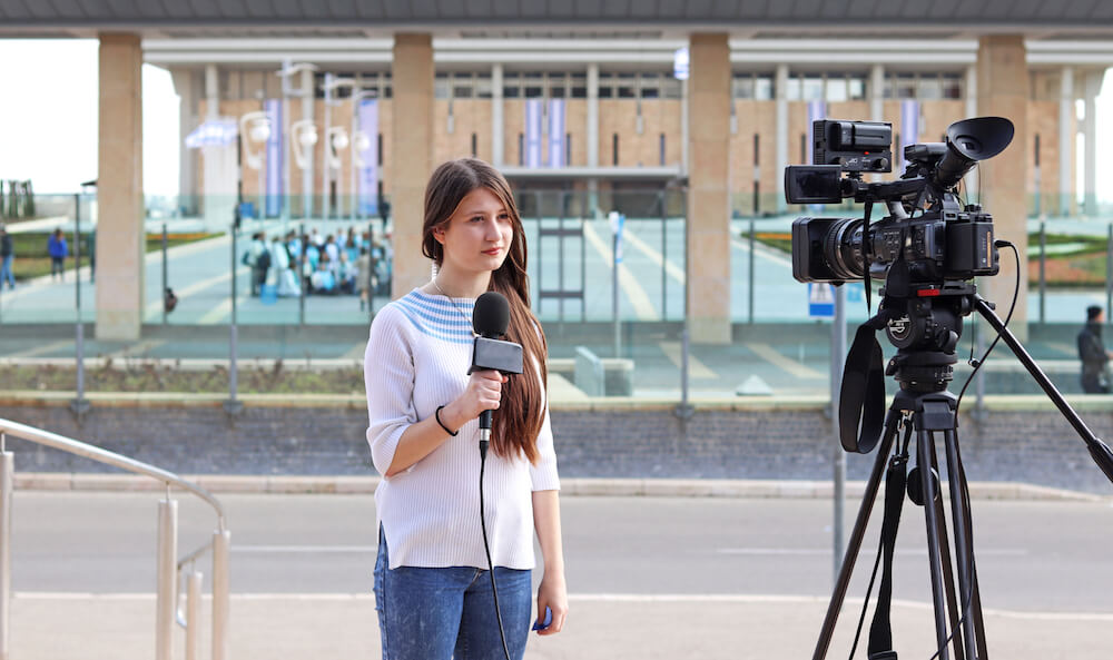 Teenage girl reporter talking in from of the Knesset