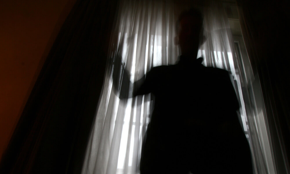 Spooky image of a man's silhouette against the light of a window