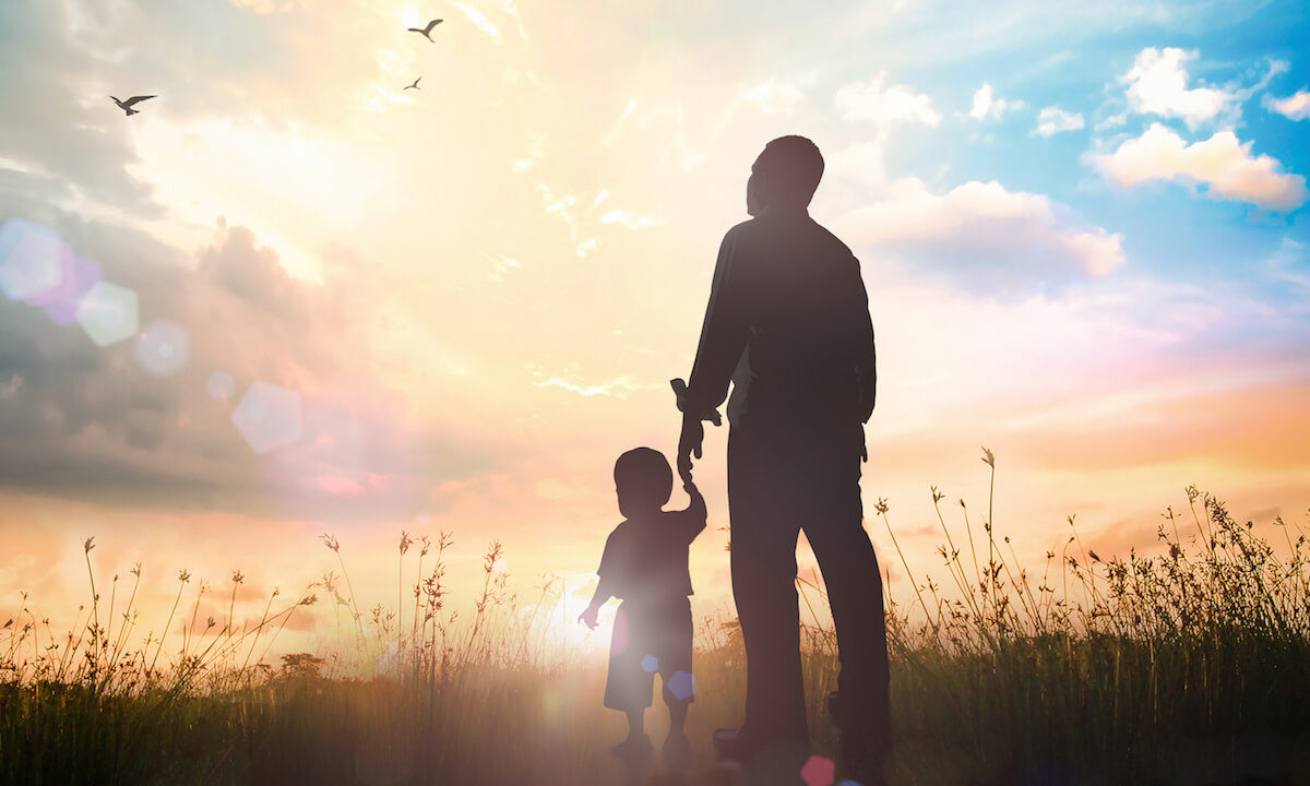 Silhouettes father and son holding hand in hand on meadow sunset background