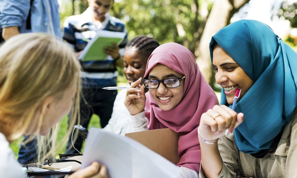 Diverse children studying outdoors