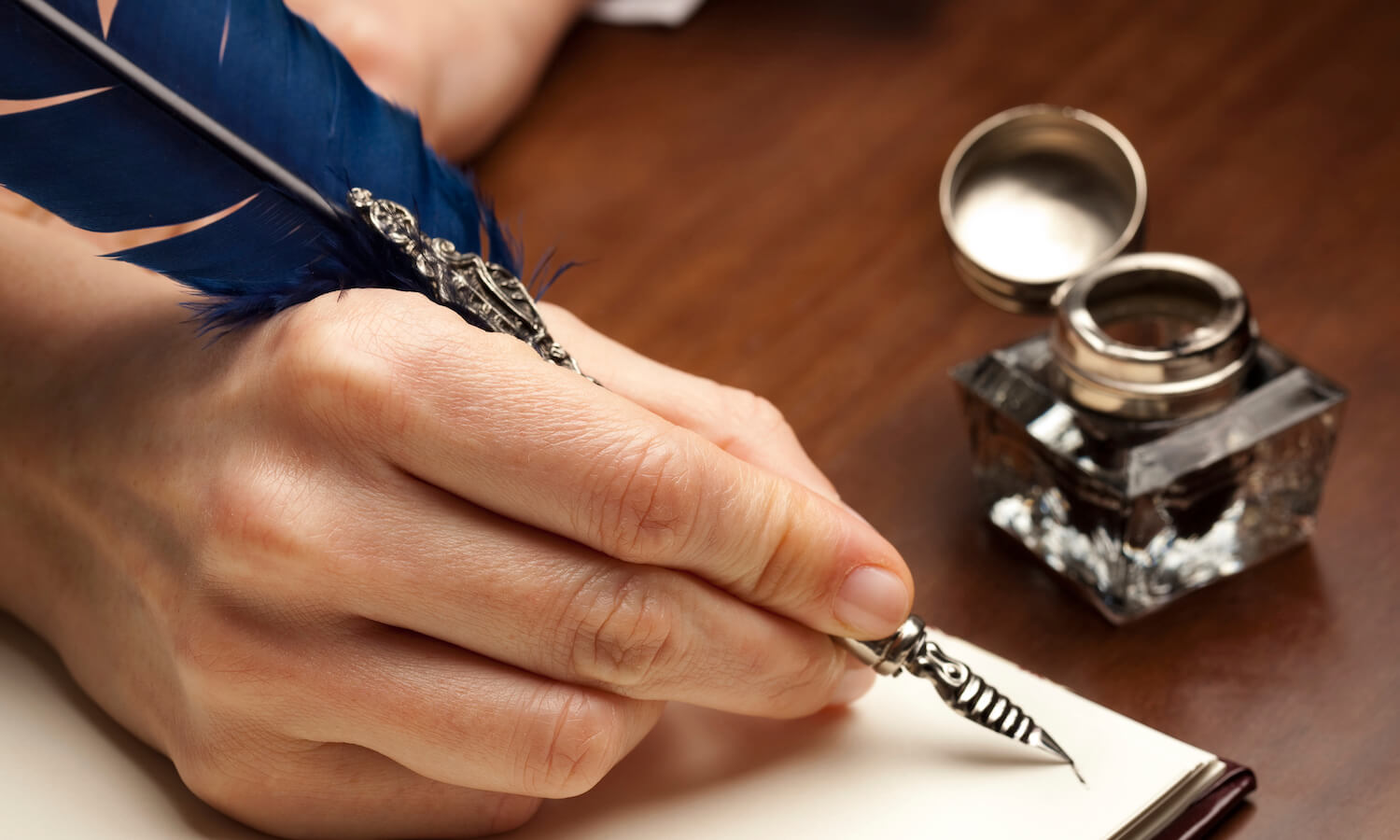 Close-up of woman's hand writing with quill pen on a blank page of a diary; inkwell nearby on the table