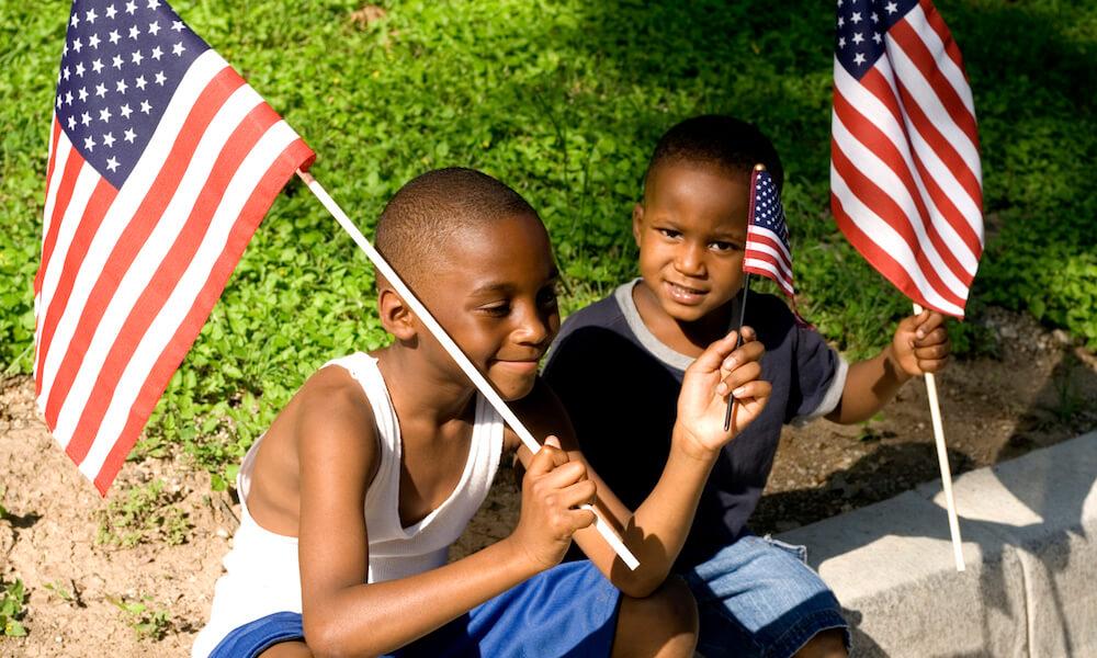 Two boys waving American flags