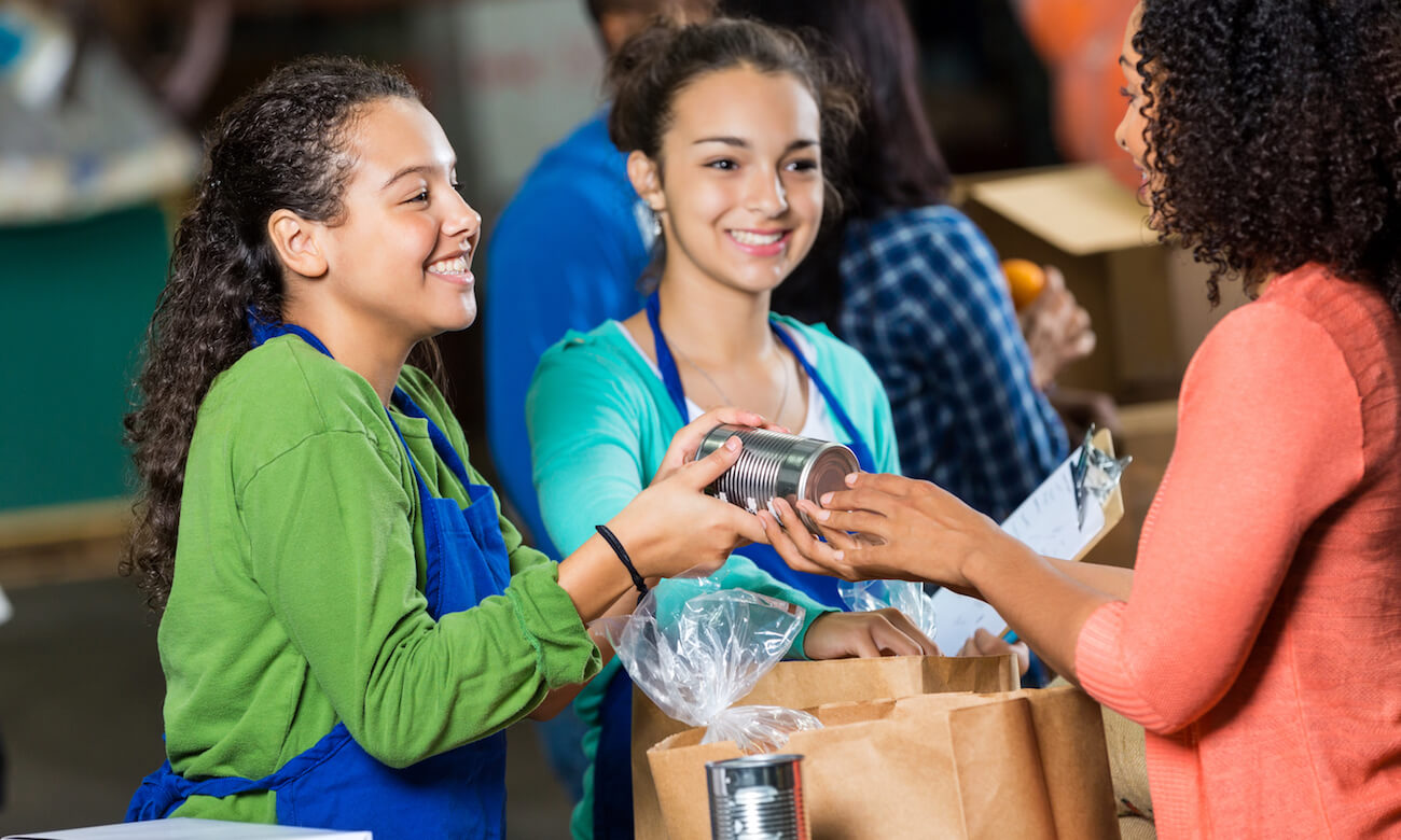 African American woman gives a canned food items to young volunteer. The woman is also donating various grocery items that are inside a paper bag. The volunteers smile as they receive the donations. Volunteers are working in the background.