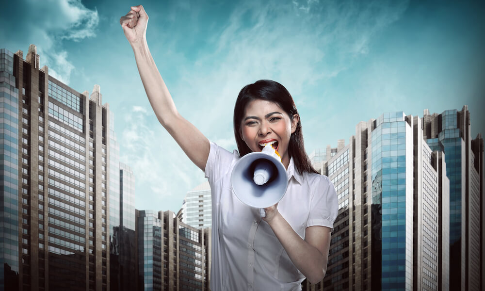 Asian business woman talk loud using megaphone