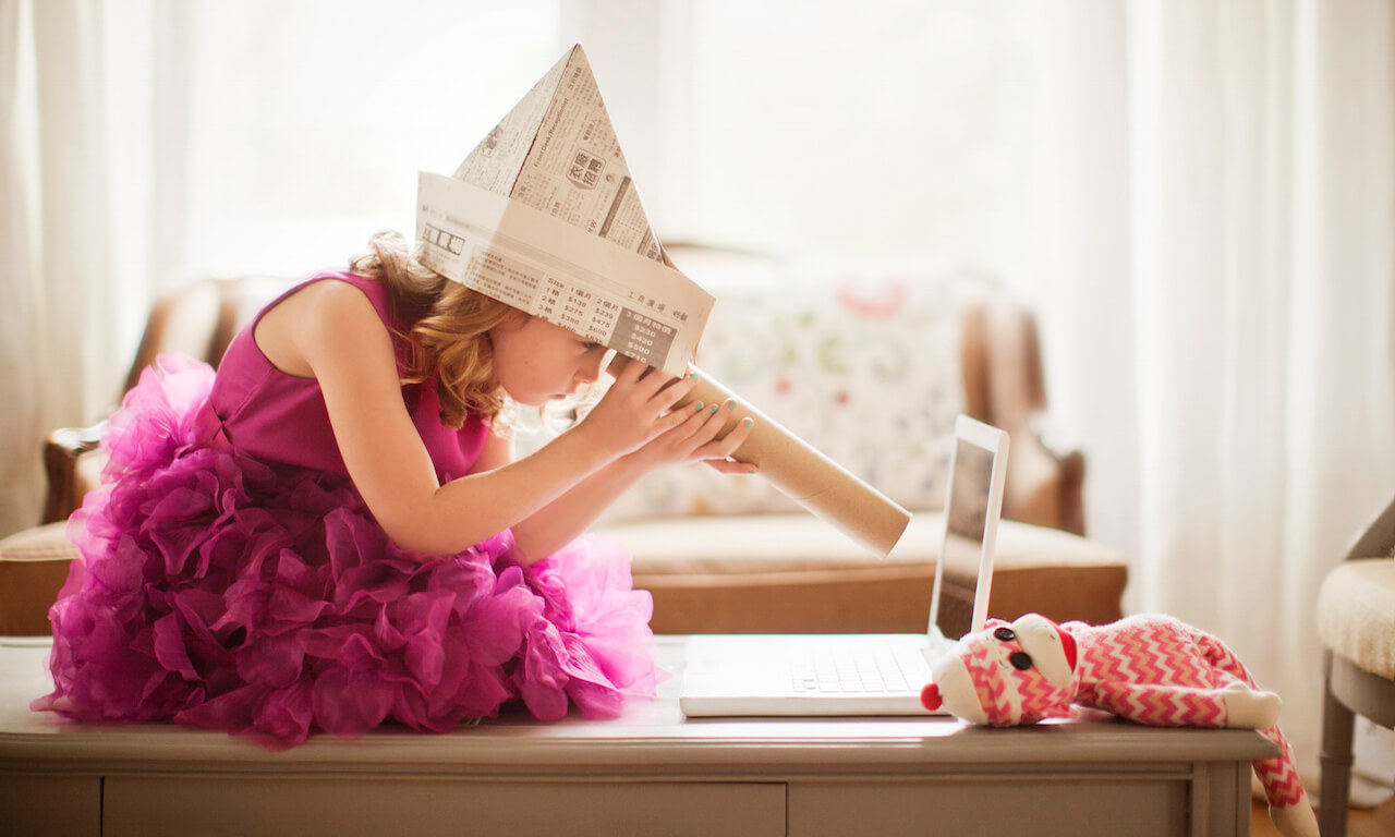 Young girl (6-7 years old) in a pink dress wearing a newspaper hat is using a kitchen roll as a telescope, looking at a computer screen while sitting on a table; sock monkey on table