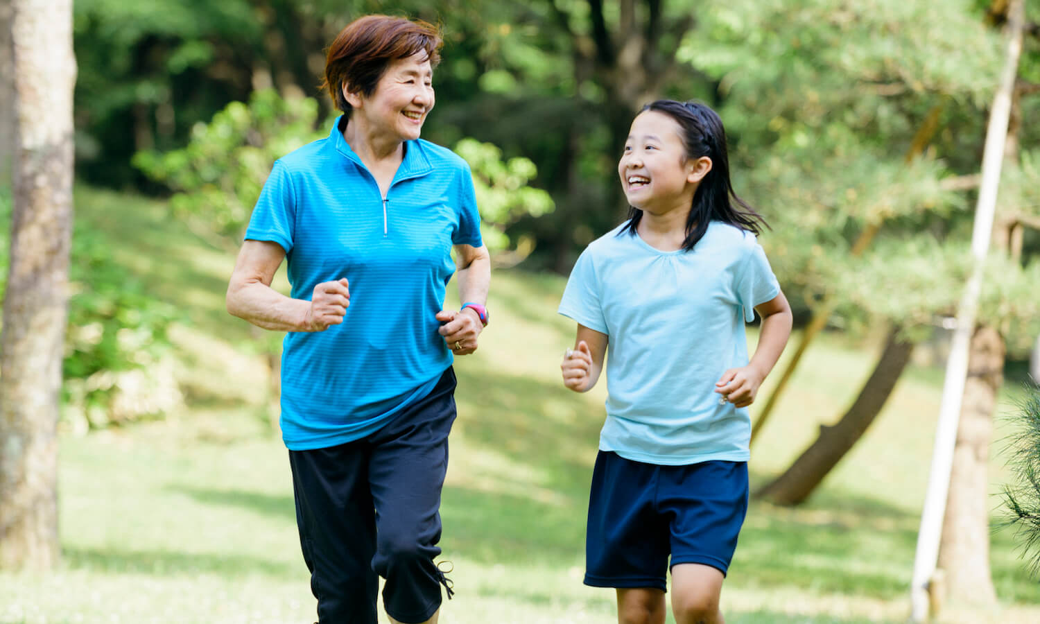 Japanese grandmother and granddaughter run through park together. Asian female senior and child runners.