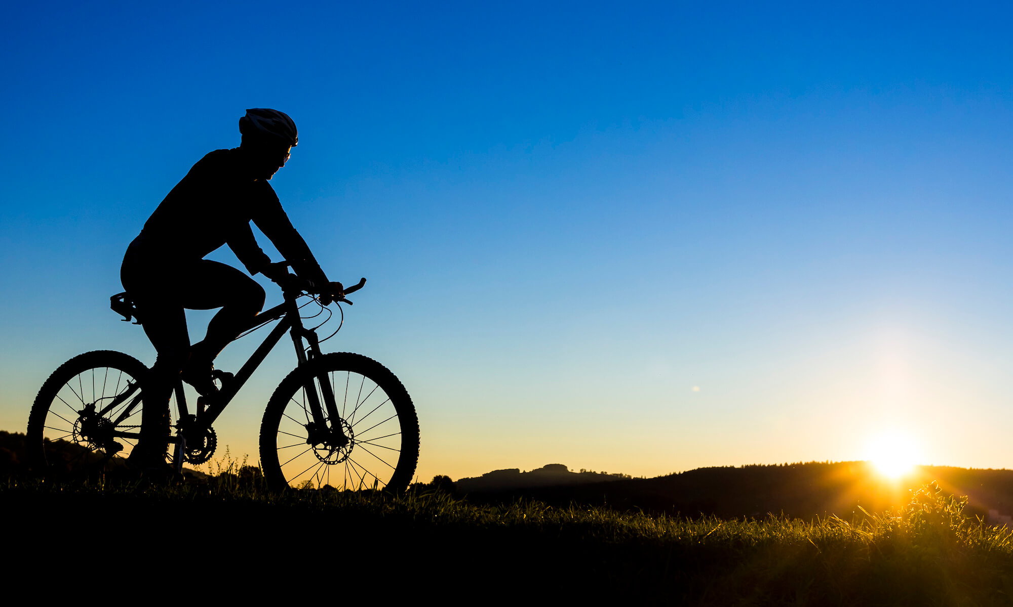 Germany, Winterbach, cyclist on a mountain bike at sunset