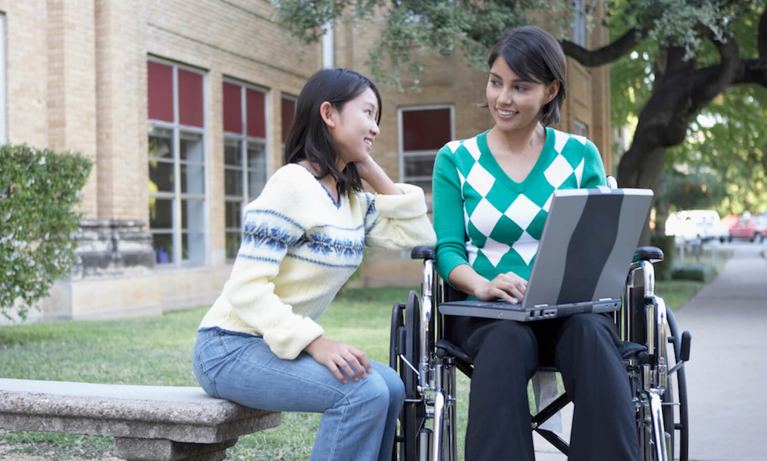Two female students in front of a laptop