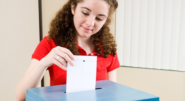 Young woman placing vote in ballot box