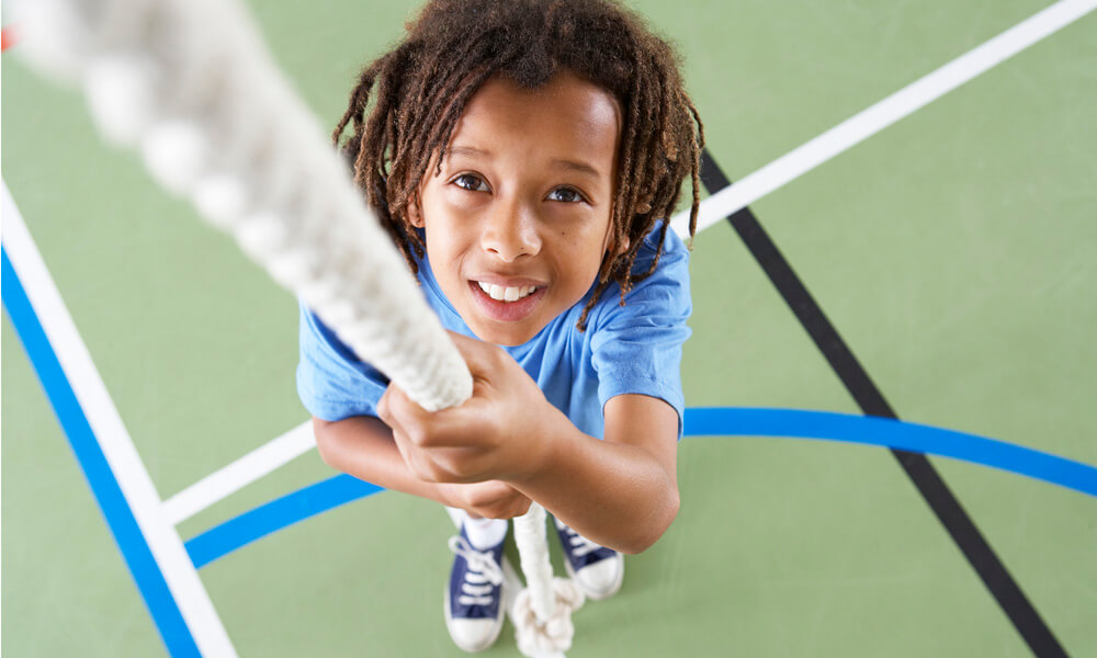 Boy holding a hanging rope in a gymnasium, looking up and preparing to climb the rope