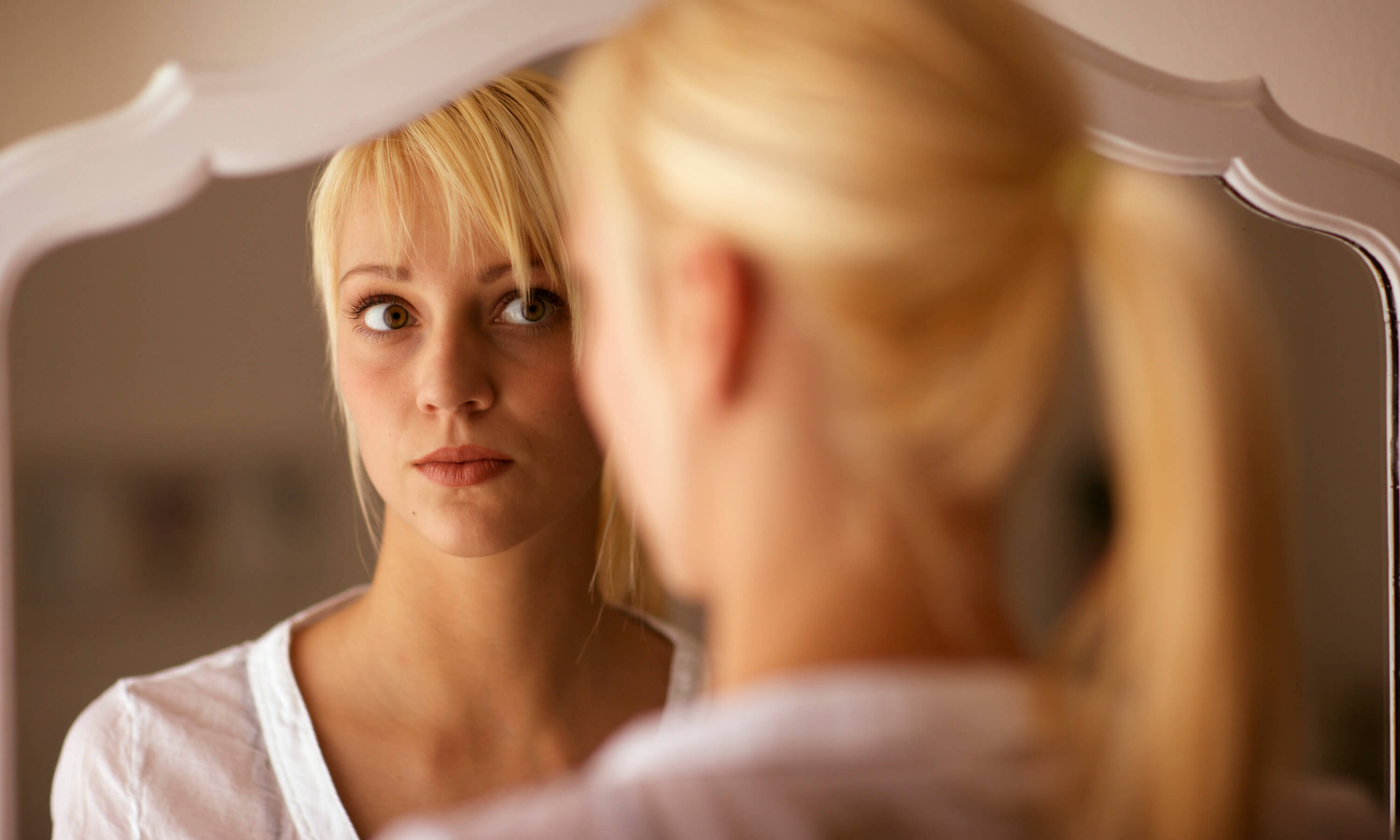 Young Blond Woman Looking in Mirror