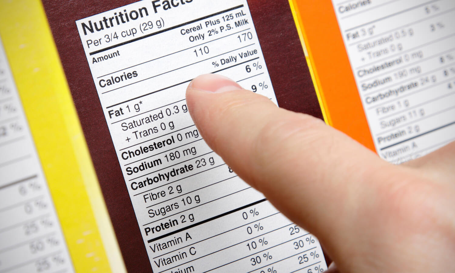 Concerned shopper checks the nutrition labels of various boxes of cereal
