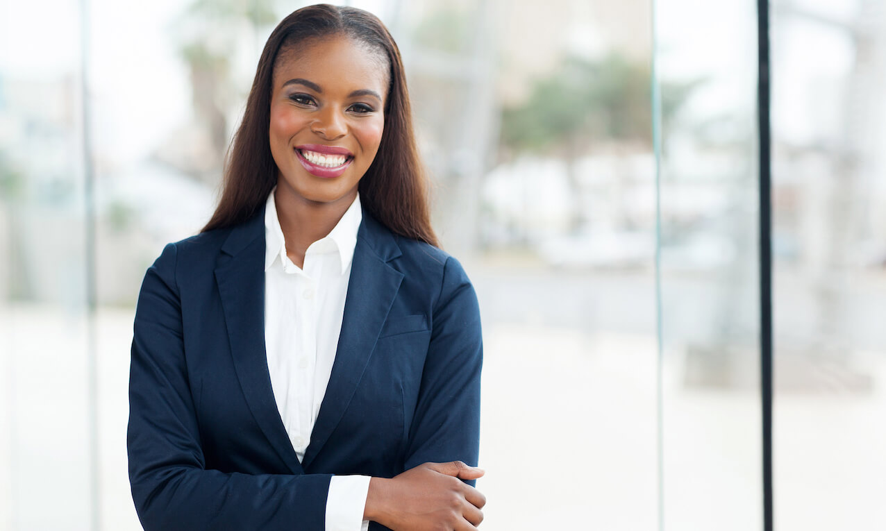 Attractive African American corporate worker standing in office