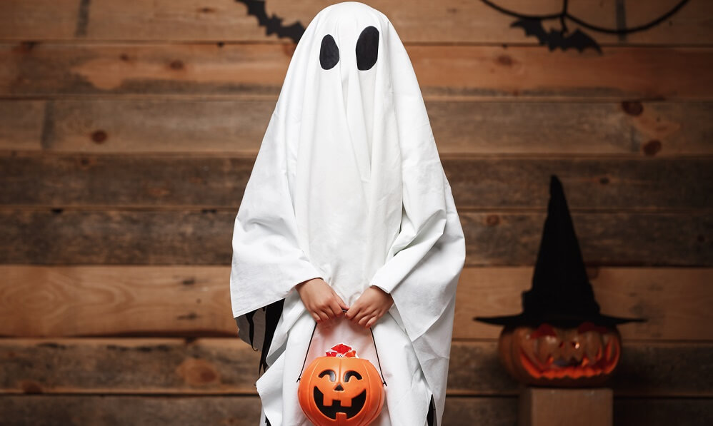 Child dressed as a ghost holding a plastic pumpkin for trick or treating
