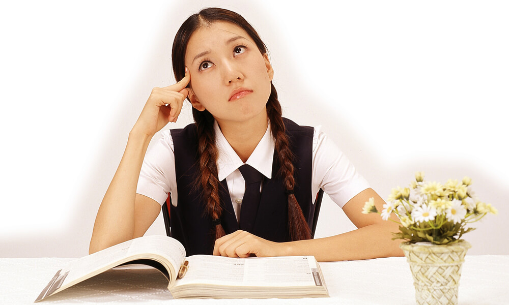 Teenage schoolgirl in uniform sitting at a desk with an open book on it, thinking