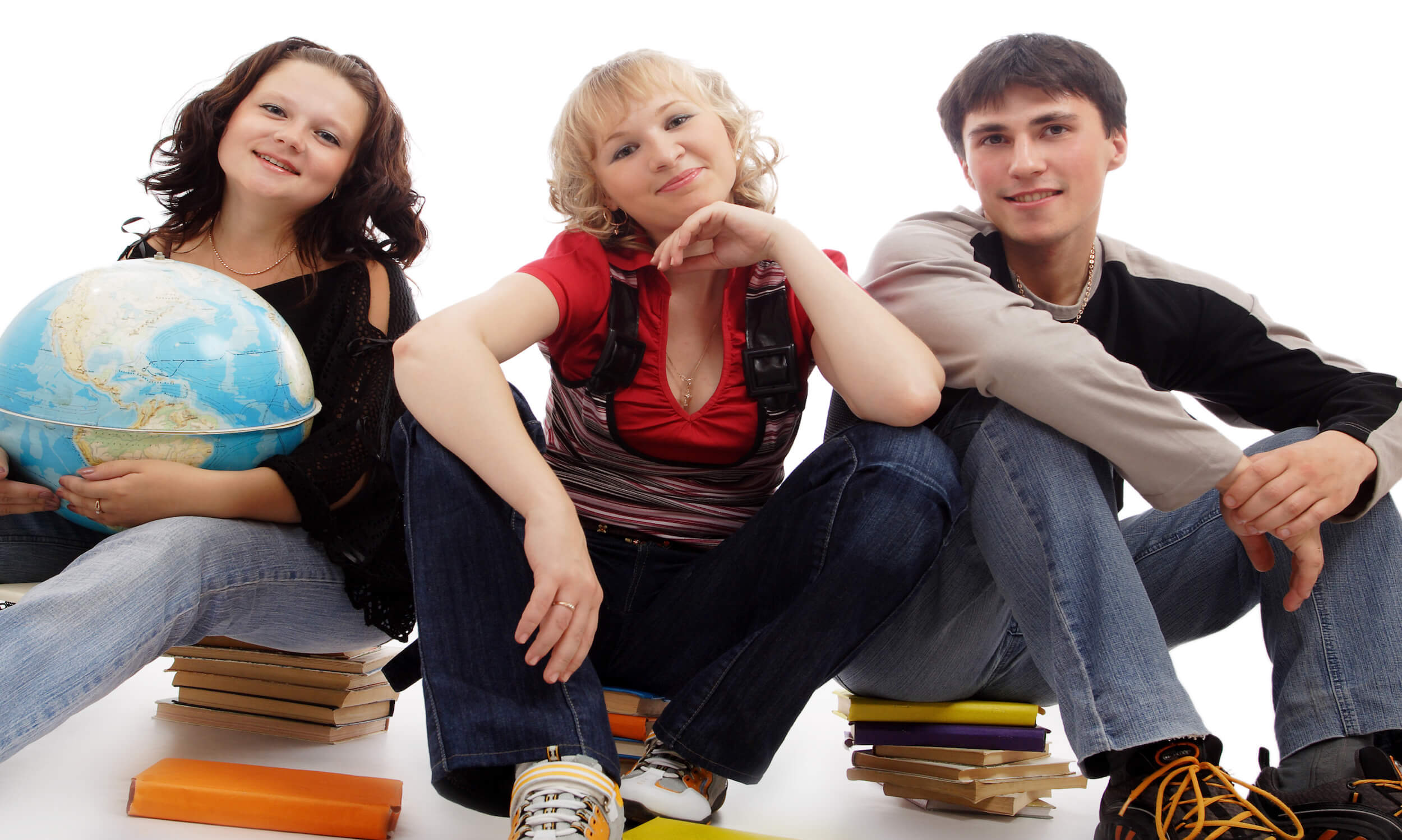 Teenagers sitting on school books and one holding a globe