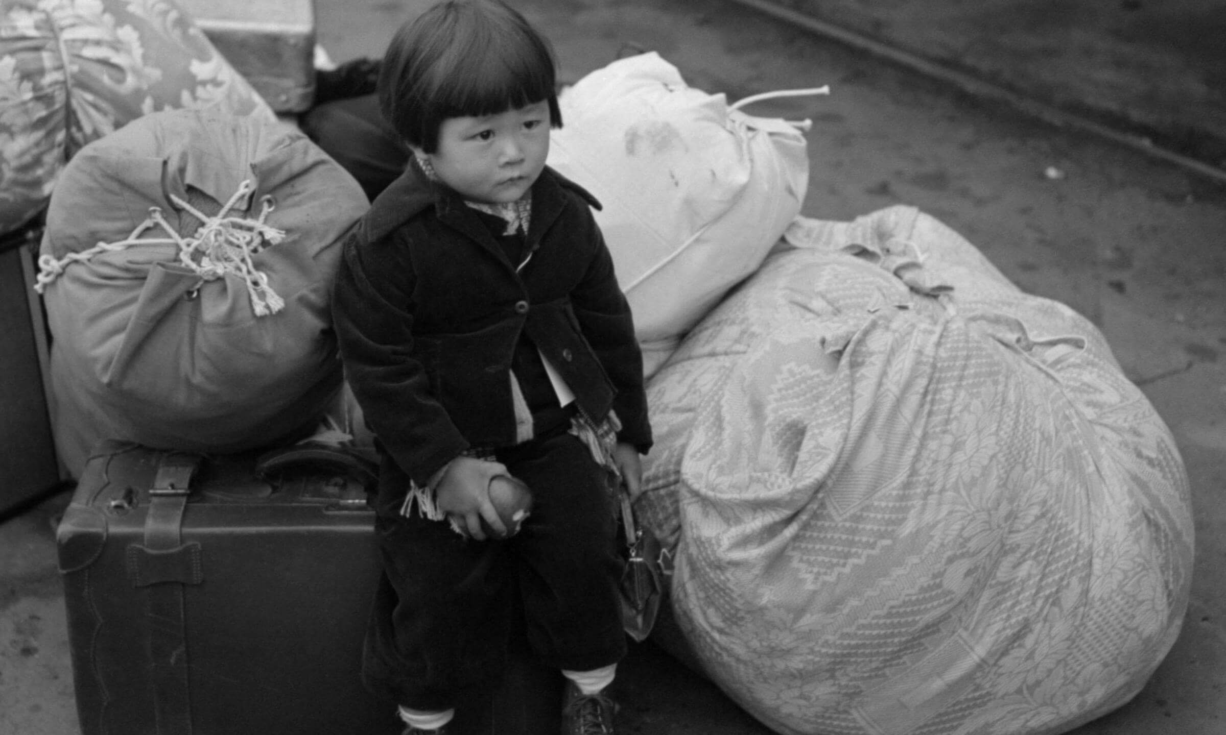 Japanese-American internee. Little child being evacuated with his parents to Owens Valley Internment Camp Manzanar over 200 miles Los Angeles