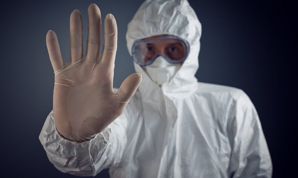 Medical worker in quarantine suit holding up hand