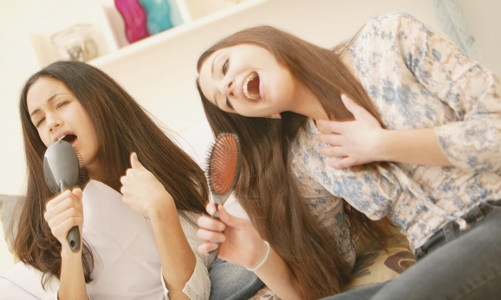 Teenage girls pretending to sing into their hairbrushes as microphones