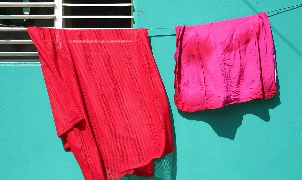 Colorful laundry against a green wall