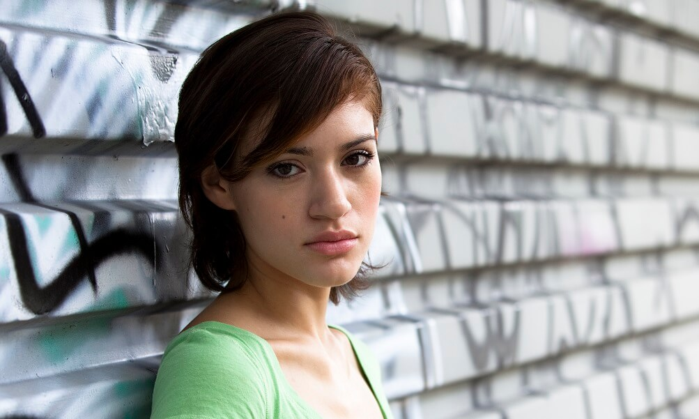 Outdoor portrait of a young Latina standing against a tin fence covered with graffiti.