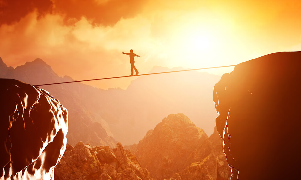 Man walking and balancing on rope over precipice in mountains at sunset.