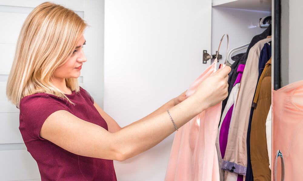 Young woman chooses clothes in a closet