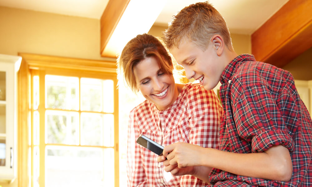 Mother, son using smart phone in kitchen laughing