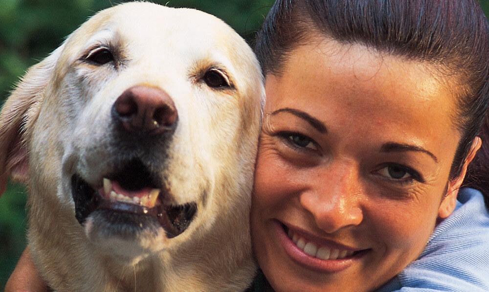 woman hugging golden retriever dog