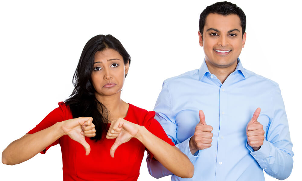 Closeup portrait of a young man and young woman. The young man is smiling optimistic, showing thumbs up; the young woman is frowning, showing thumbs down.