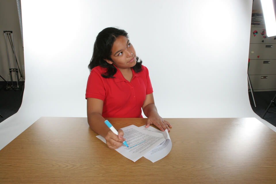 Hispanic girl looking thoughtful while highlighting a paper