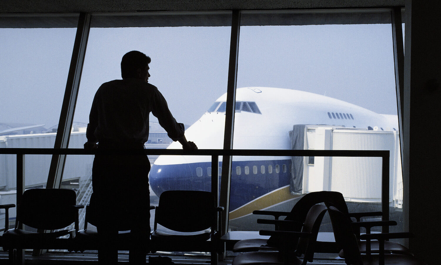 Silhouette of a man staring at airplanes on the tarmac through an airport window