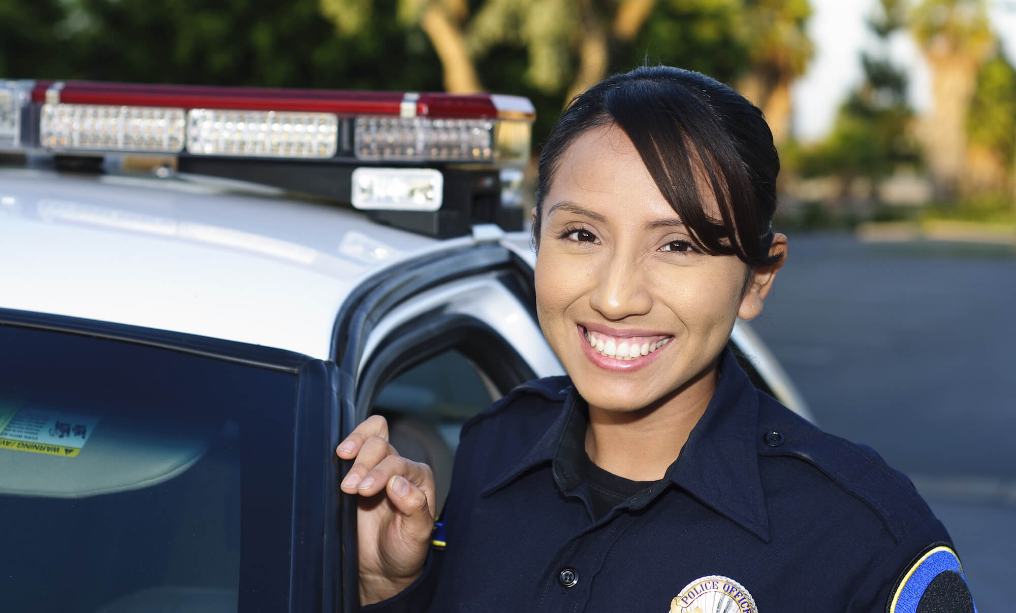 Female Hispanic police officer smiling next to her car