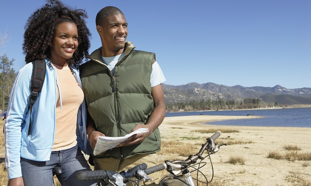 A couple in the wilderness with bicycles and a map