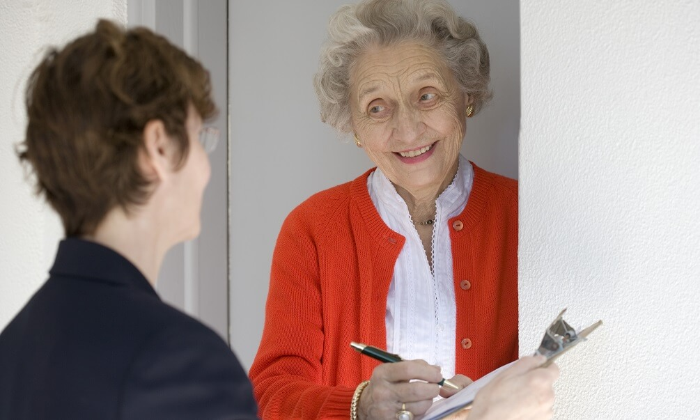 Woman answering a survey at her front door
