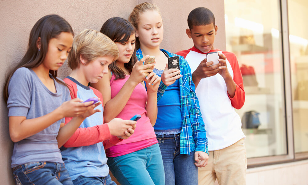 Group of kids staring at cell phones