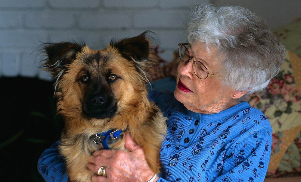 elderly woman embracing dog