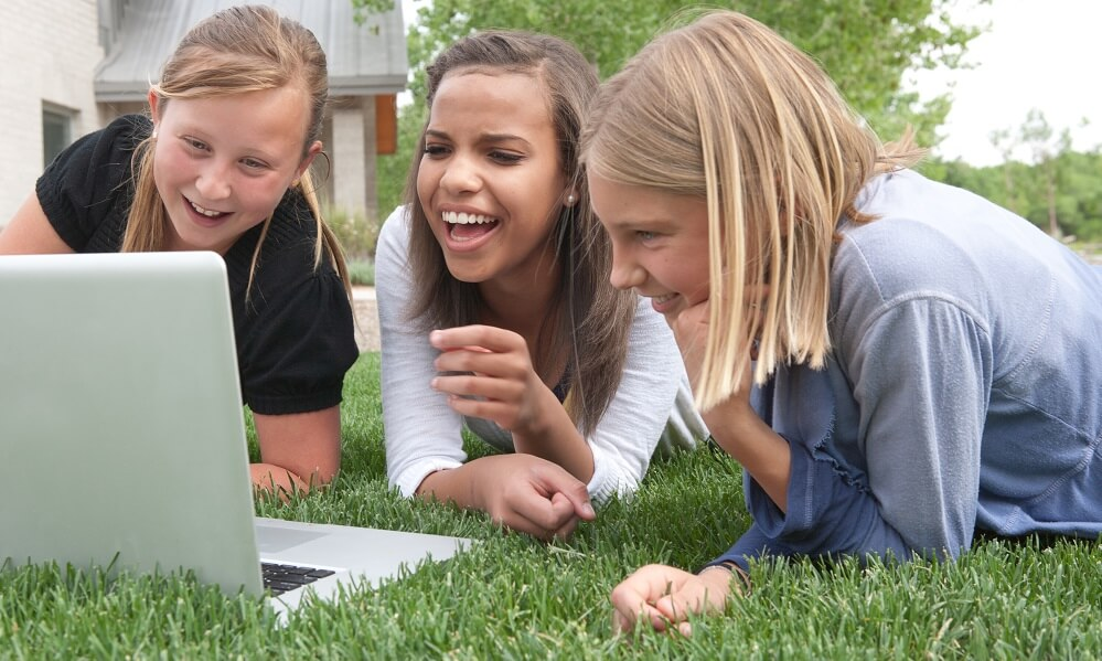 Three middle school students (12-15 years old) watch a funny video outdoors on a laptop computer and laughing